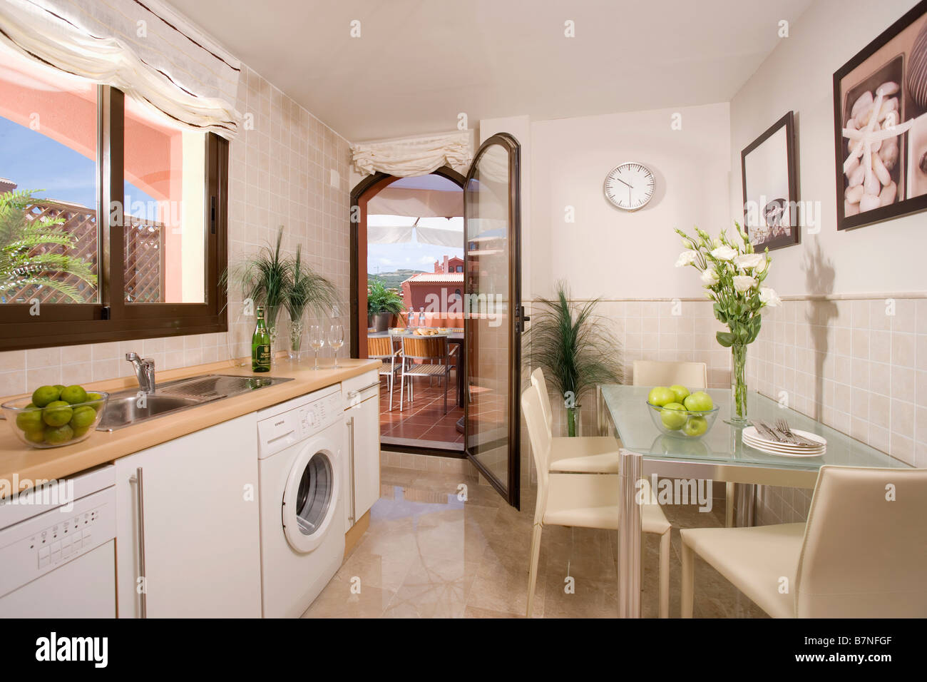 Glass table and beige chirs in small galley kitchen diner in Spanish ...