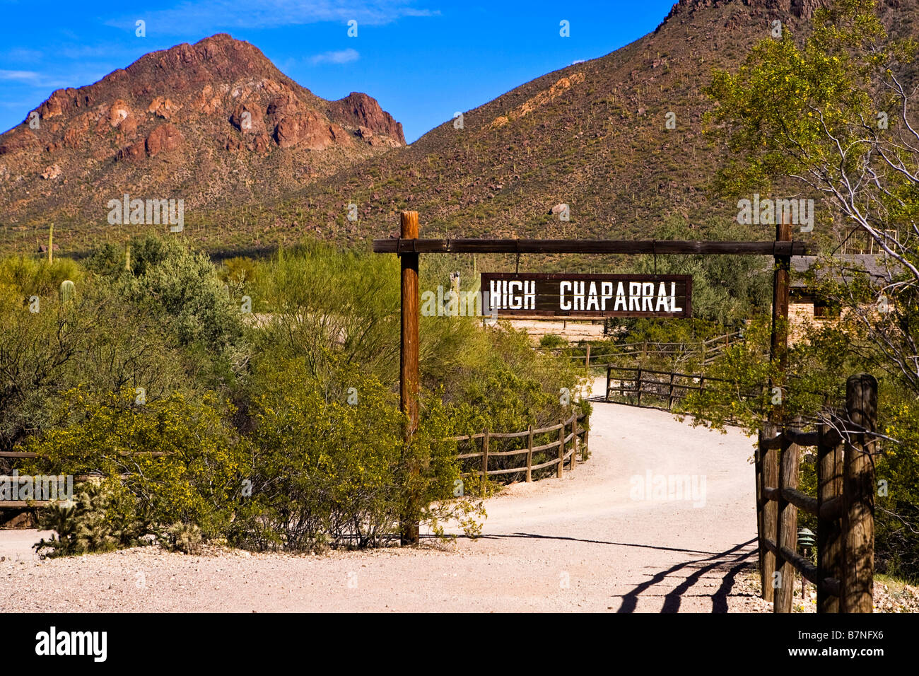Image looking down the road and through the hanging overhead sign for the High Chaparell film location in Old tucson - Stock Image