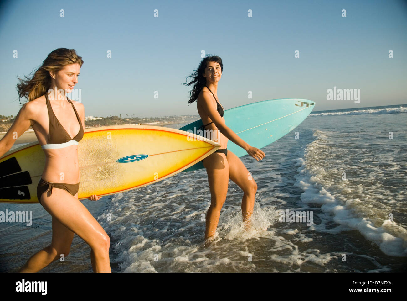 Two Young Female Surfer Girls Walk Out To The Surf Zuma