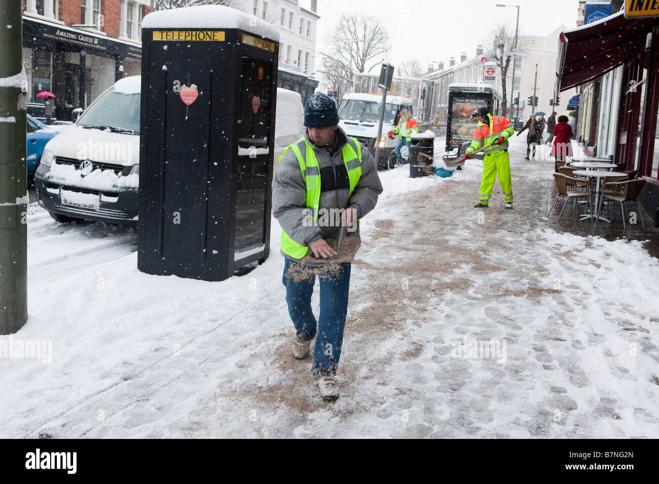 Barnet Borough Council workers spread grit and salt on the pavement near East Finchley Underground Station - Stock Image