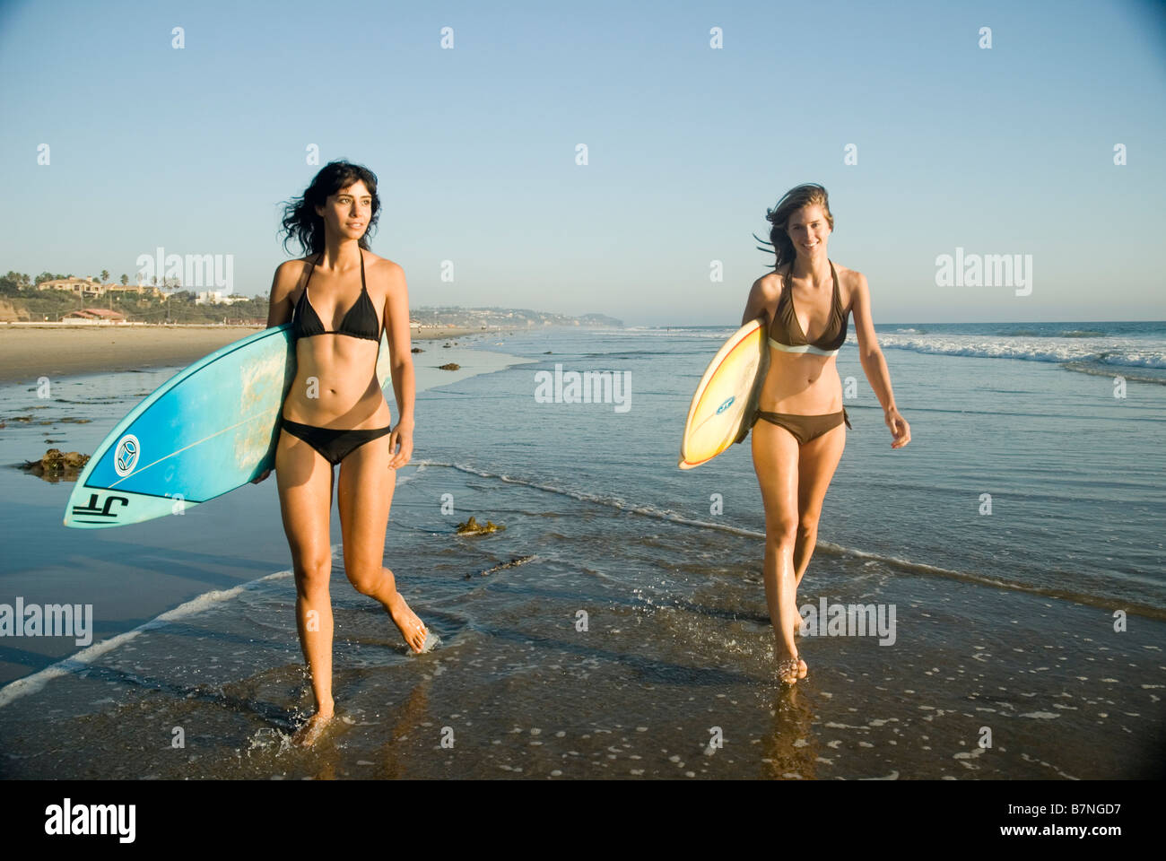 Two Young Female Surfer Girls Walking Out To The Surf Zuma