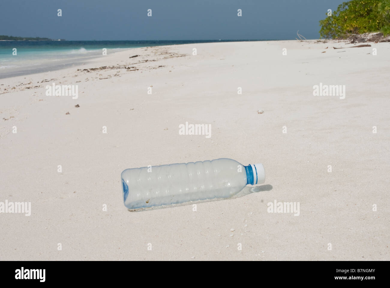 Plastic bottle washed up on a tropical beach in the Maldives. - Stock Image