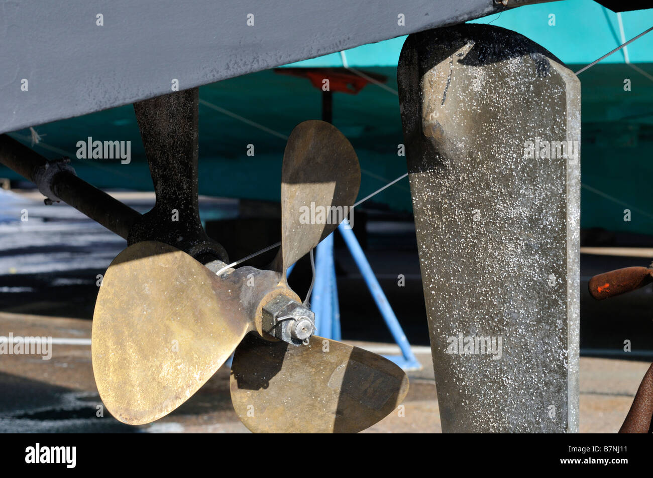 Powerboat bronze prop shaft and rudder showing pitting corrosion and barnacle growth - Stock Image
