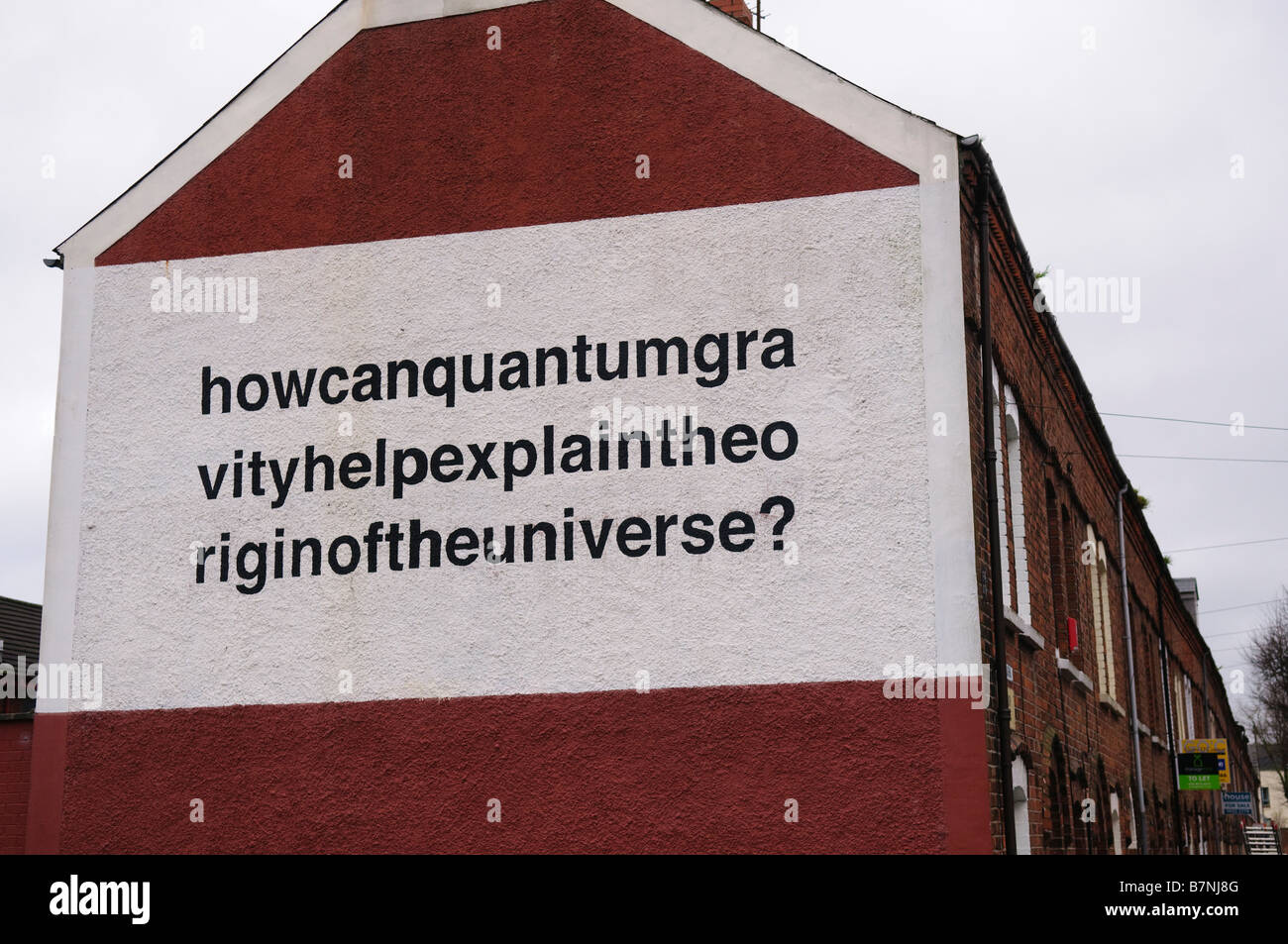 Mural in Belfast 'How can quantum gravity help explain the origin of the universe?' painted on side of terraced - Stock Image