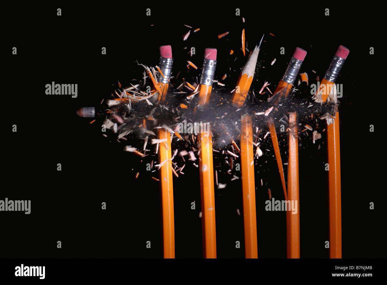 A bullet hitting pencils - Stock Image