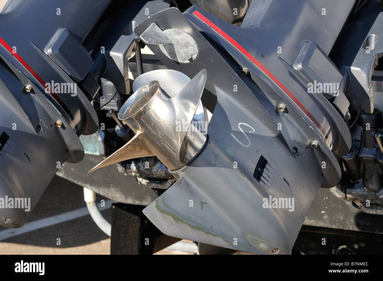 Outboard boat motor showing prop lower unit and zinc out of the water. - Stock Image