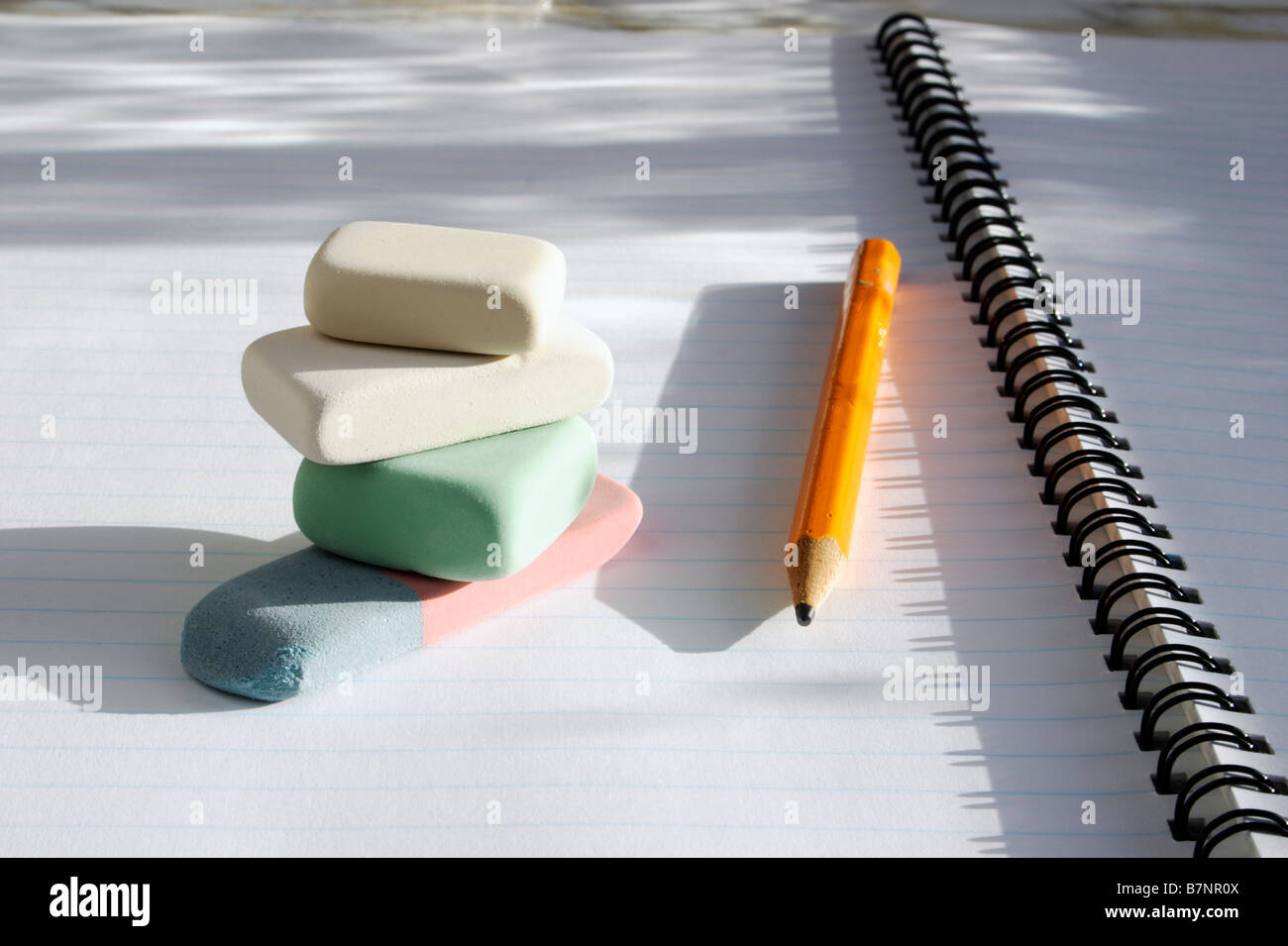 A pile of erasers and a pencil on the page of a spiral exercise book. - Stock Image