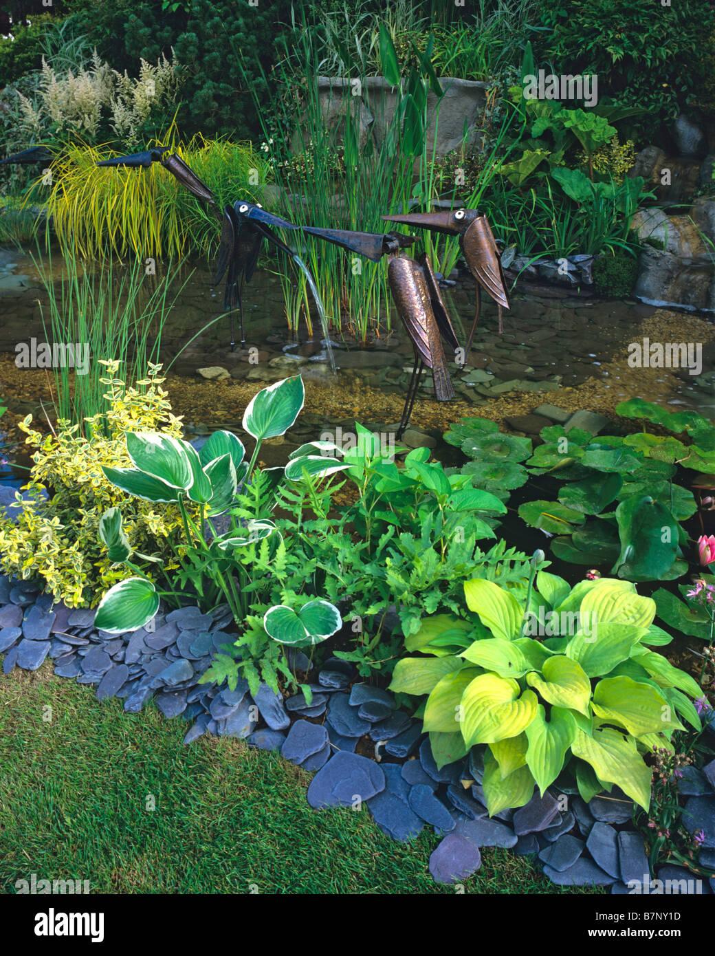 Wildlife pond with Hostas and birds sculptures - Stock Image