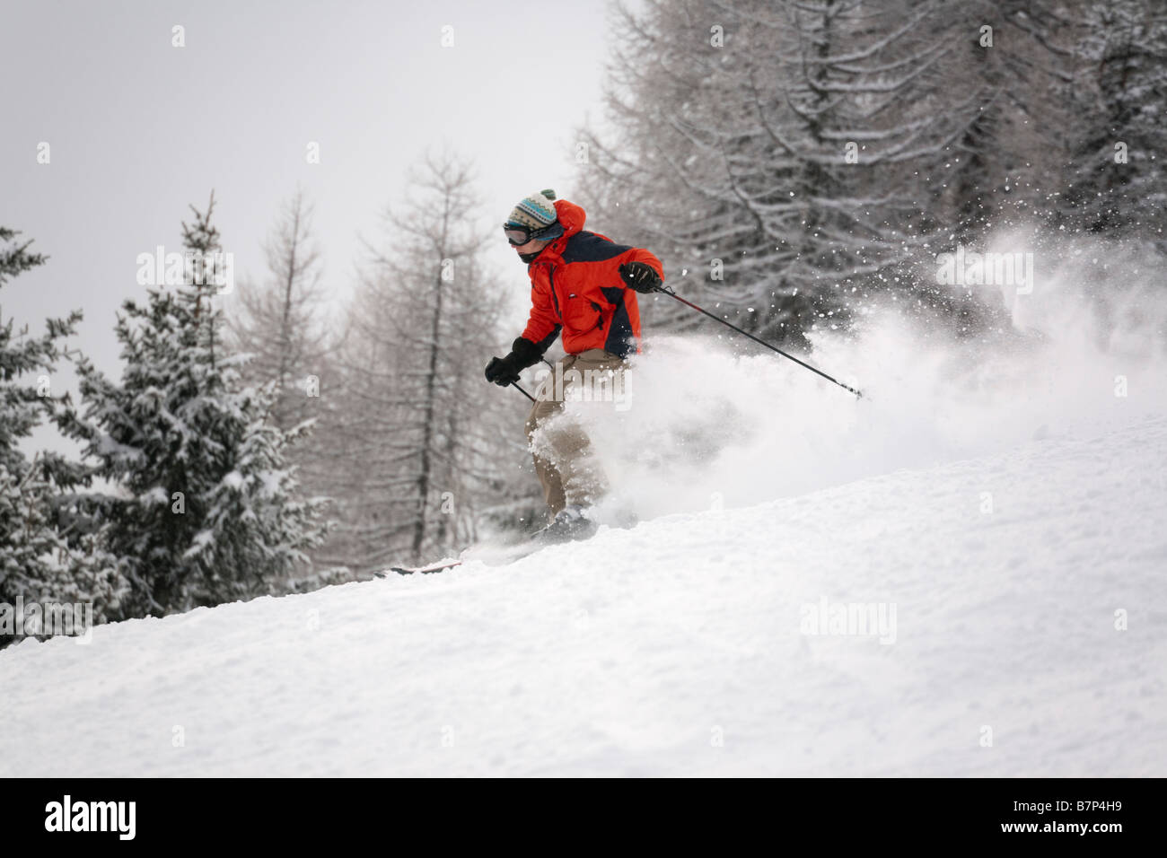 Skier wearing a red jacket skiing fast downhill in powder snow on ski slope piste in Austrian Alps. Rauris Austria - Stock Image