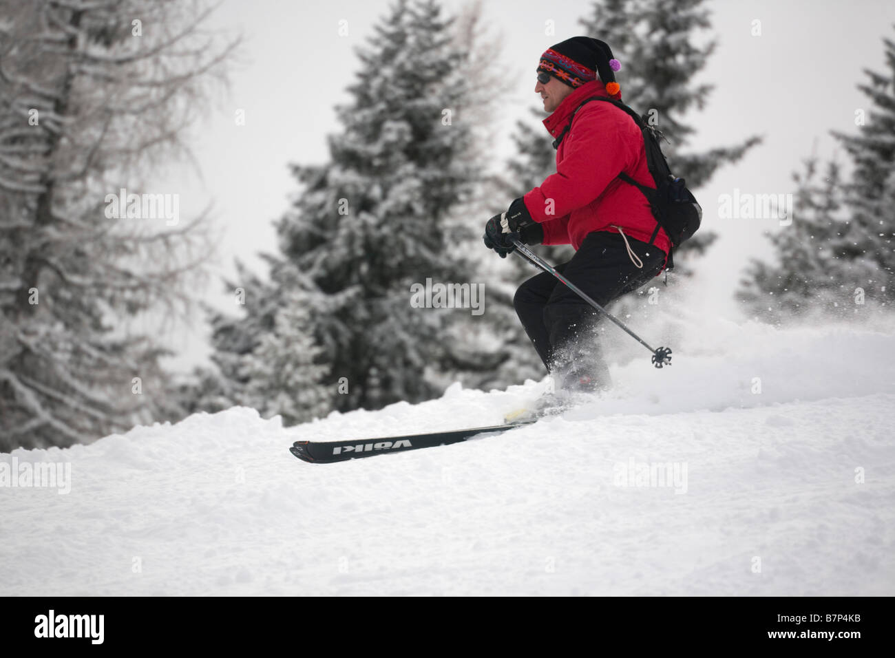 Male skier wearing a red jacket skiing fast down a mountain slope in powder snow on piste in Austrian Alps. Austria, - Stock Image