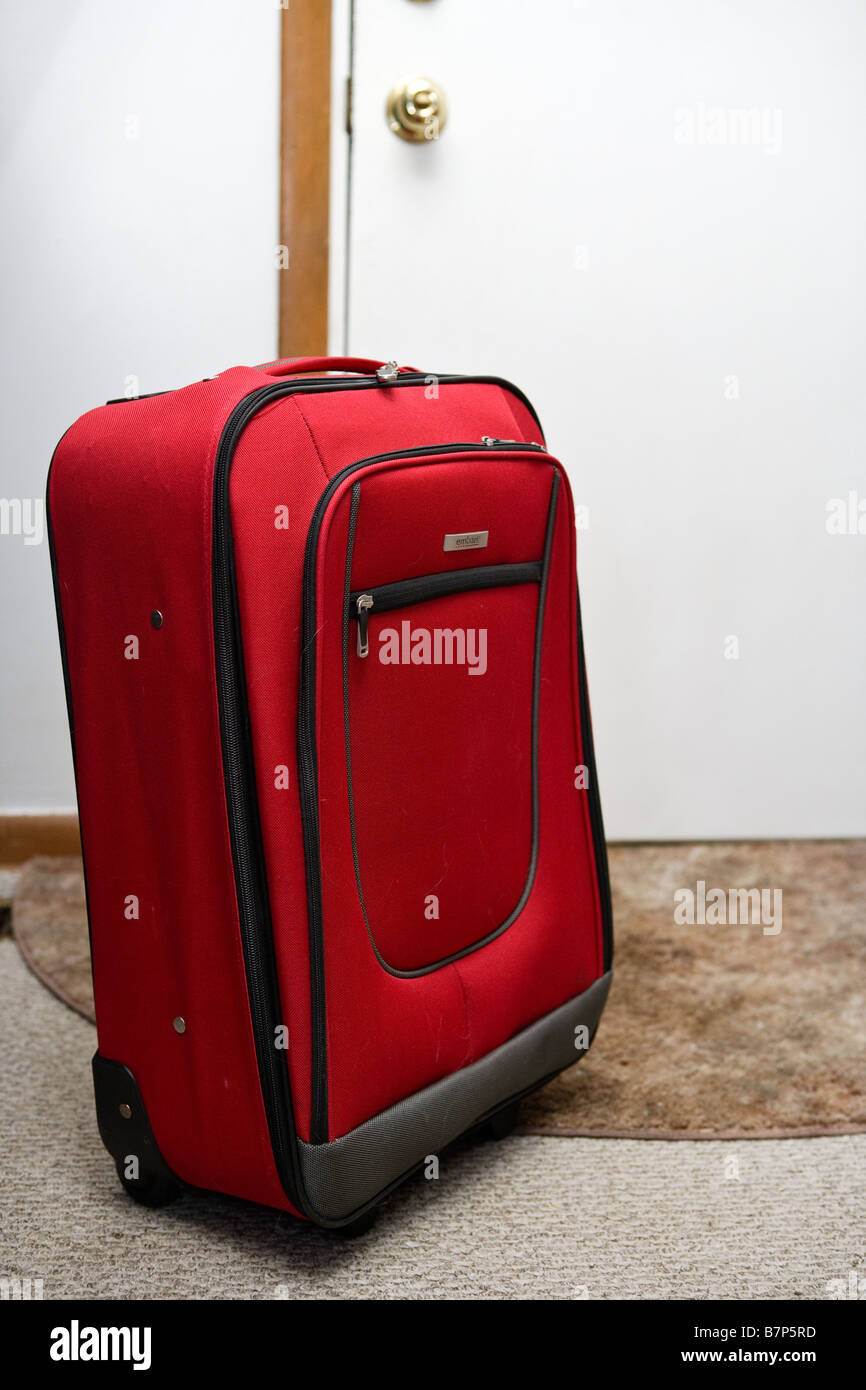 A suitcase next to the door - Stock Image