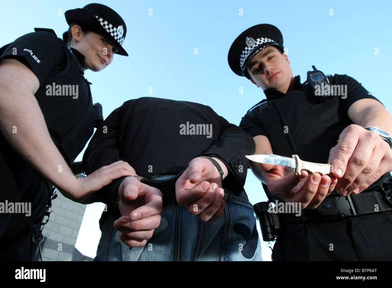 Grampian Police officers from Aberdeen, Scotland, UK, train to remove a bladed weapon from a suspect in handcuffs - Stock Image
