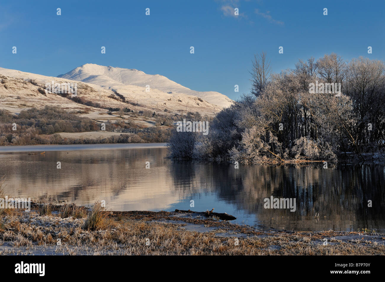 Snow covered Ben Lawers seen beyond an island in Loch Tay near Killin Perthshire Scotland UK - Stock Image