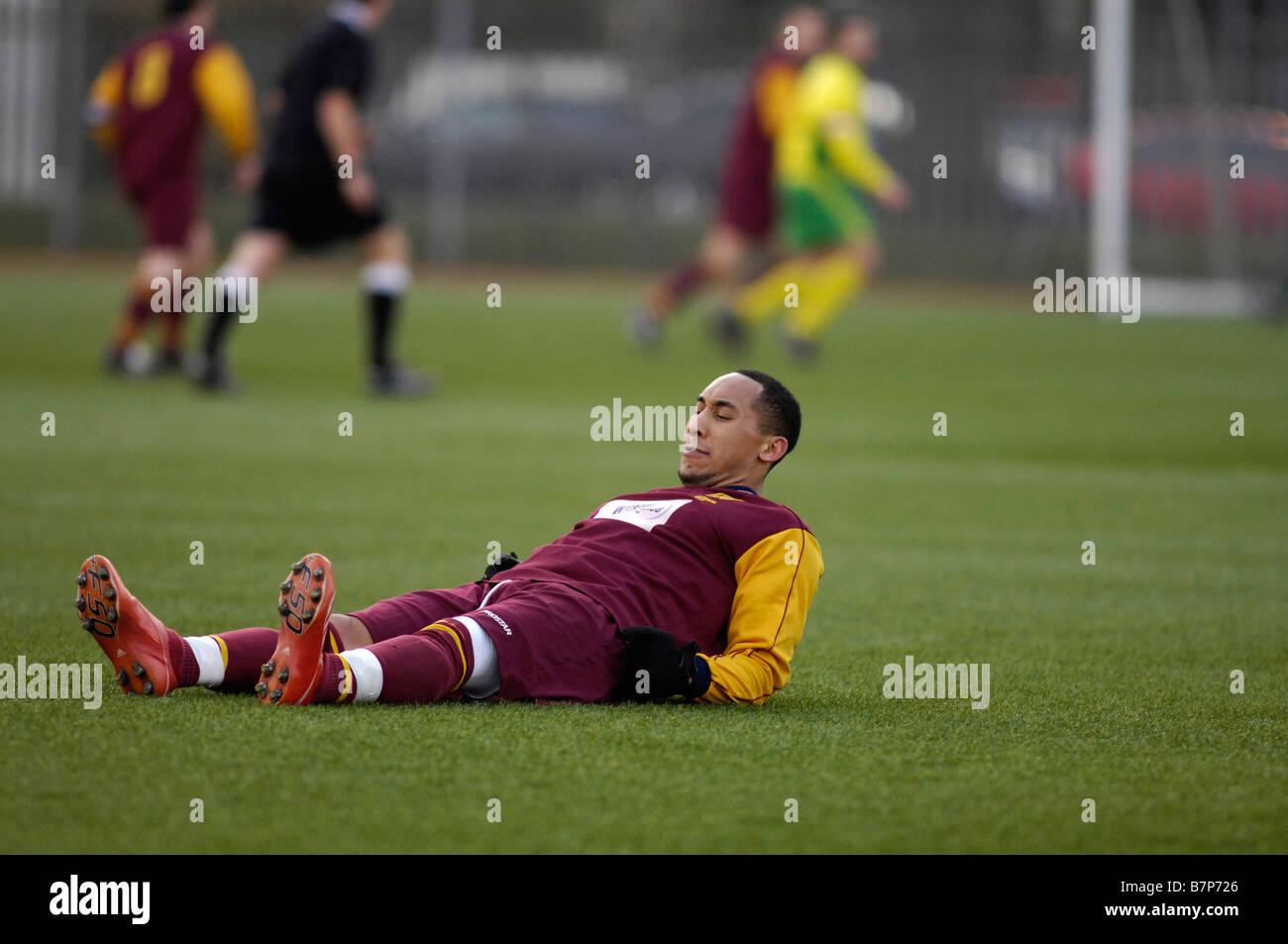 footballer suffering from cramp - Stock Image