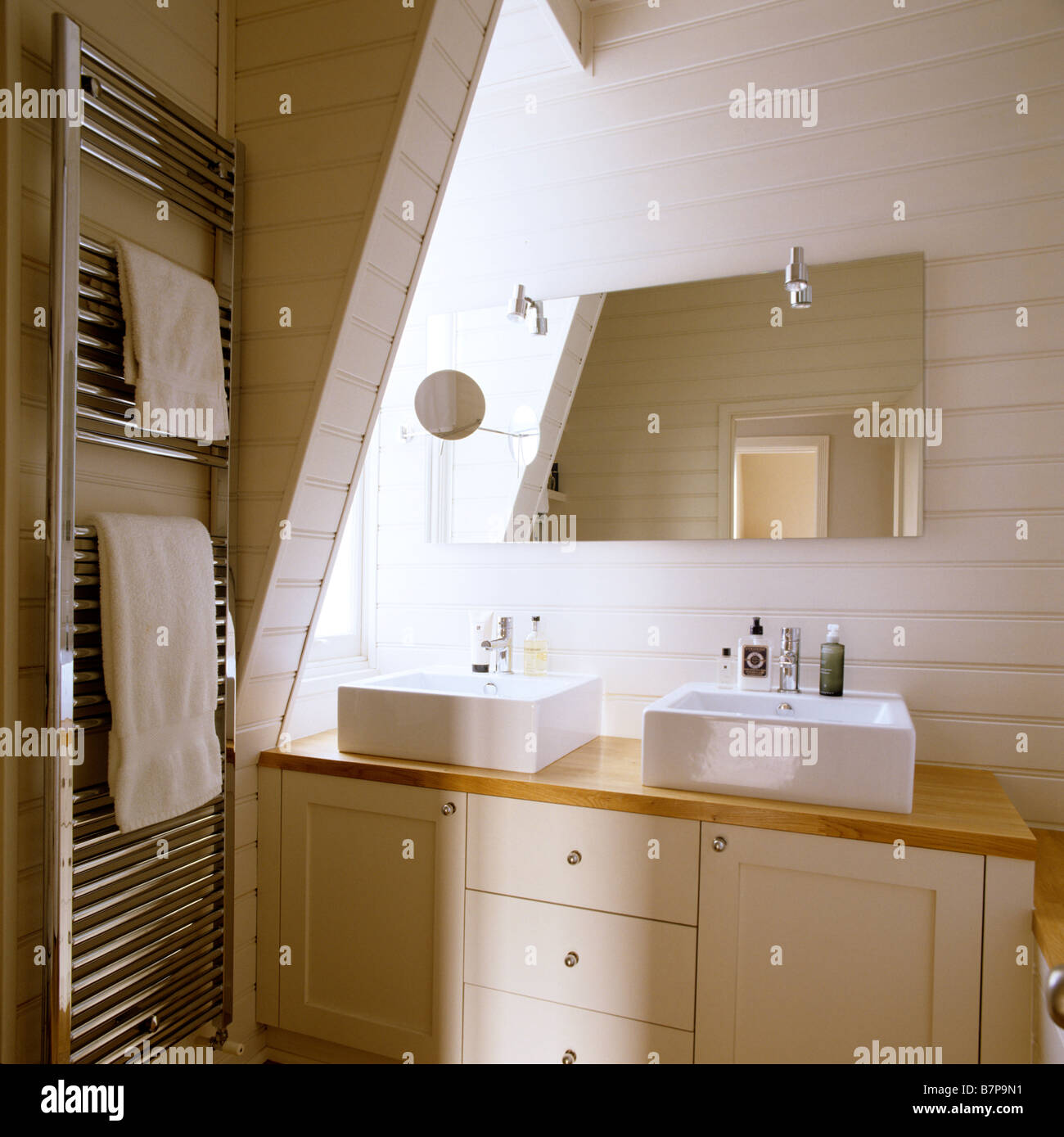 Modern wood panelled bathroom with double basin and metallic towel rail. - Stock Image