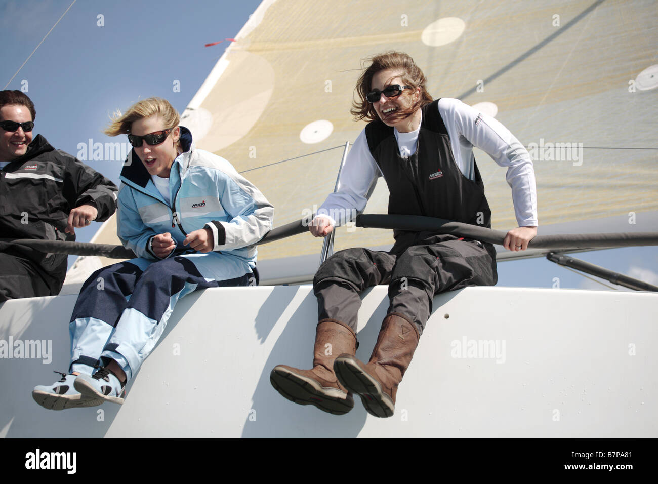 3 sailors, 2 female 1 male having fun on a yacht. - Stock Image