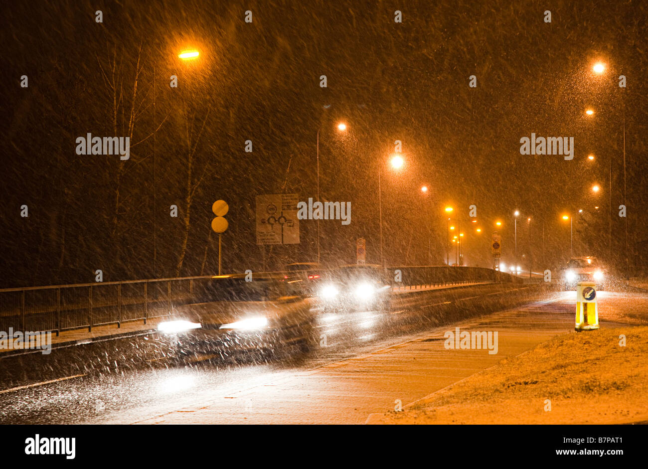 Cars driving at night in winter snowing conditions Cwmbran Wales UK - Stock Image