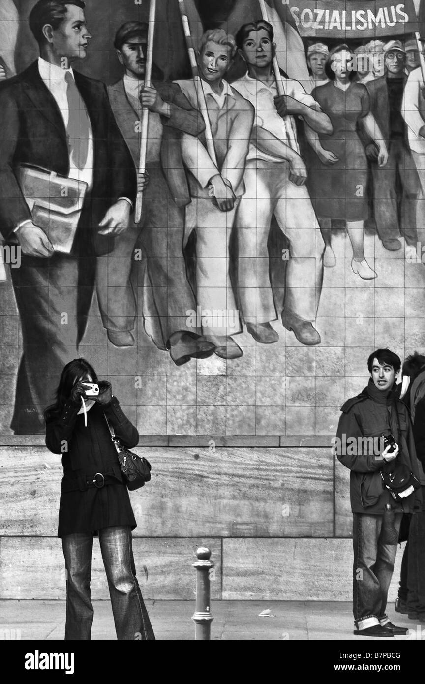 Two tourists in front of a mural painting for the glory of socialism, on the Reich Air Ministry building, Germany. - Stock Image