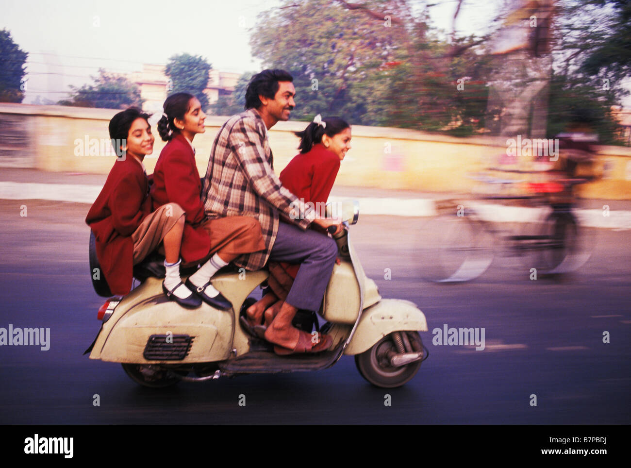 Father drives schoolgirls to school on scooter on street in Jaipur India - Stock Image