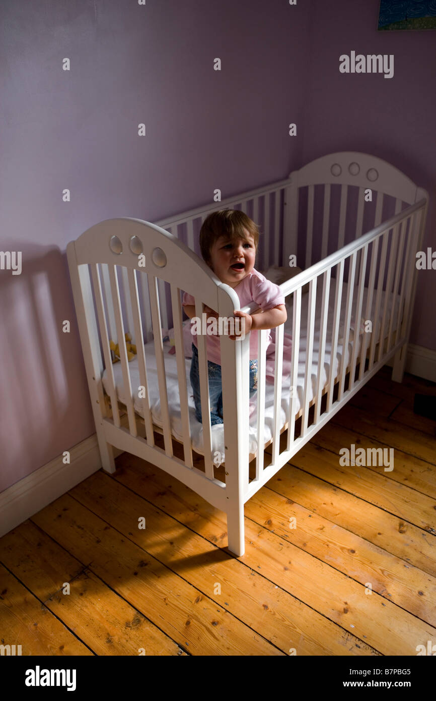A baby girl stands up in her cot and cries - Stock Image