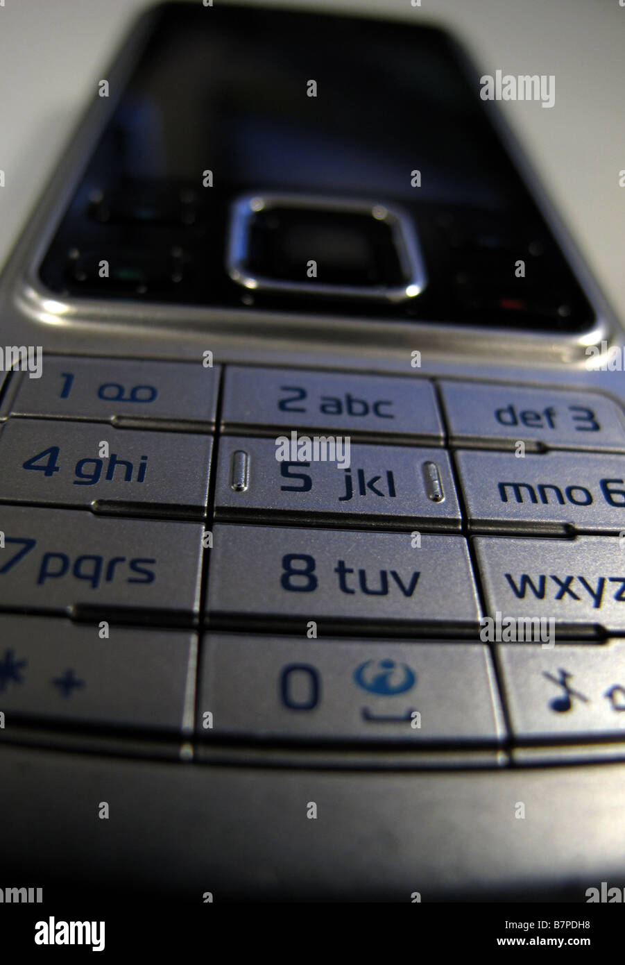 A silver Nokia mobile or cell phone is photographed on a desk in an office in central London - Stock Image