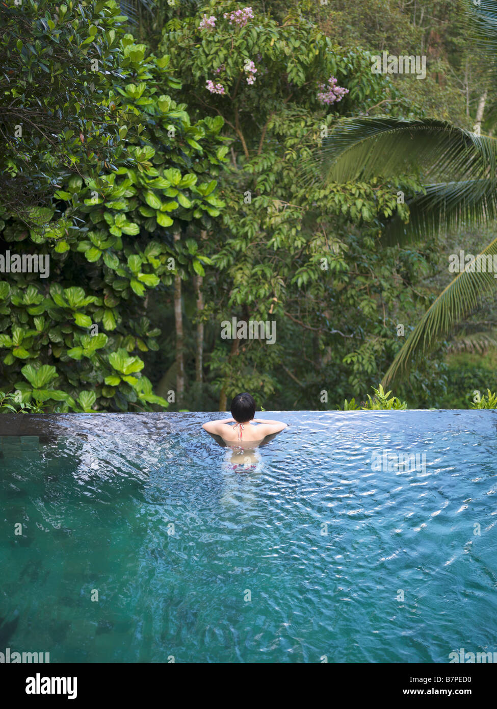 Woman Bathing In An Infinity Pool Surrounded By A Lush