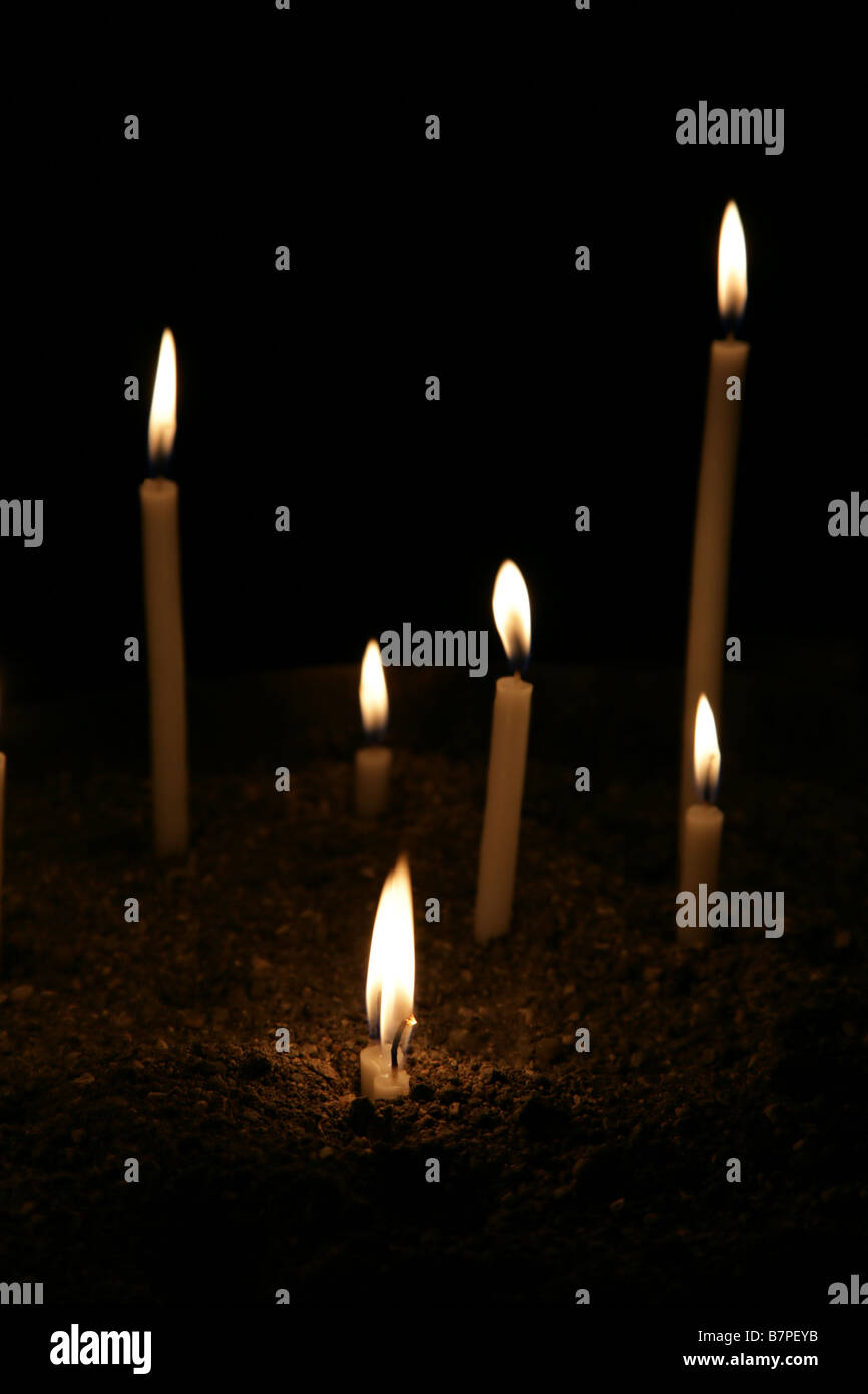 A few conflagrant candles are in darkness - Stock Image