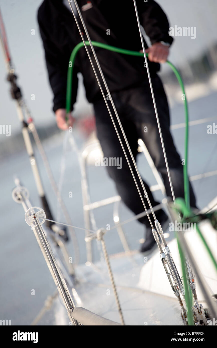 man hosing his yacht down after a voyage - Stock Image