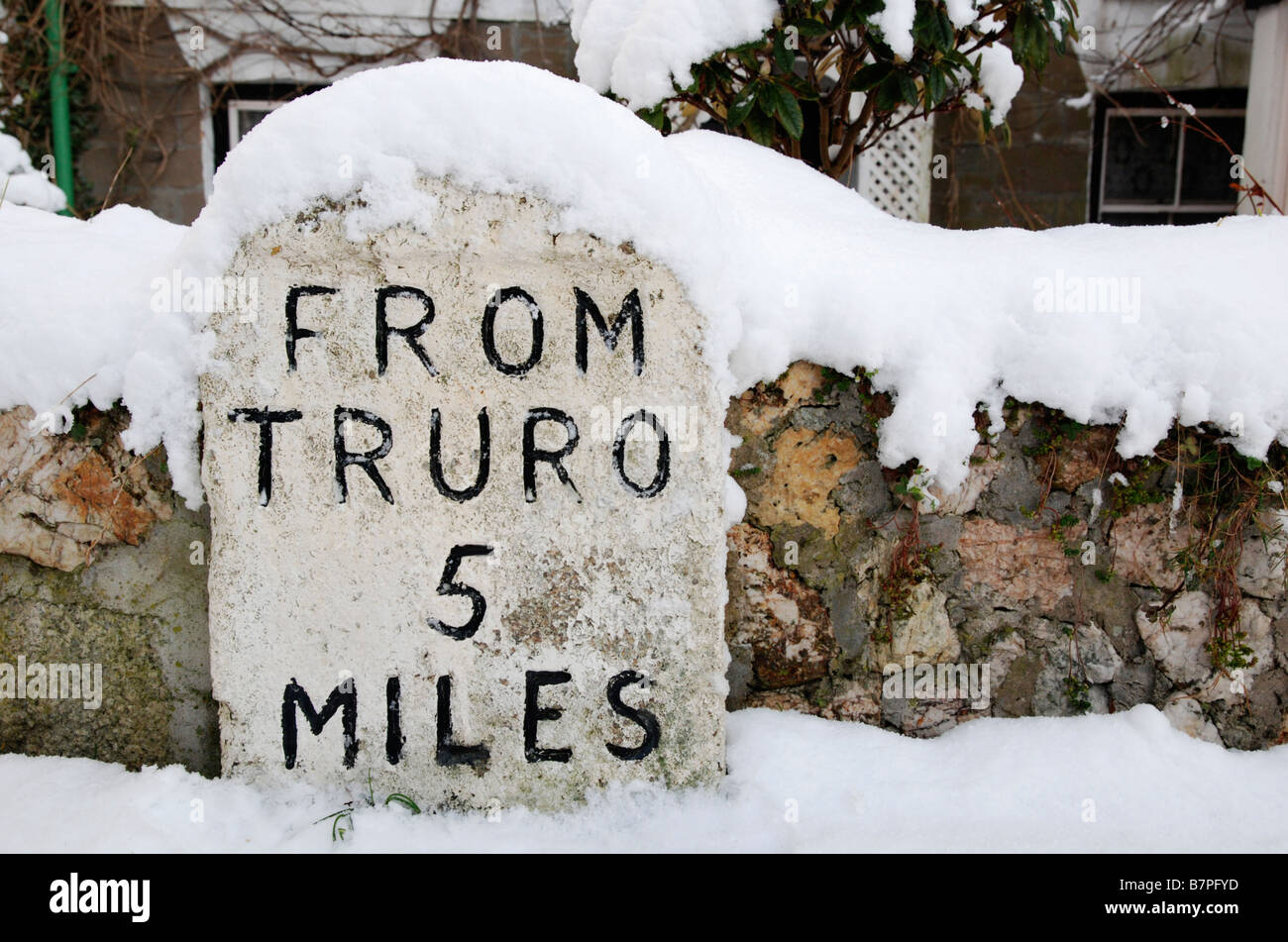 a snow covered milestone showing 5 miles to truro,cornwall,uk - Stock Image