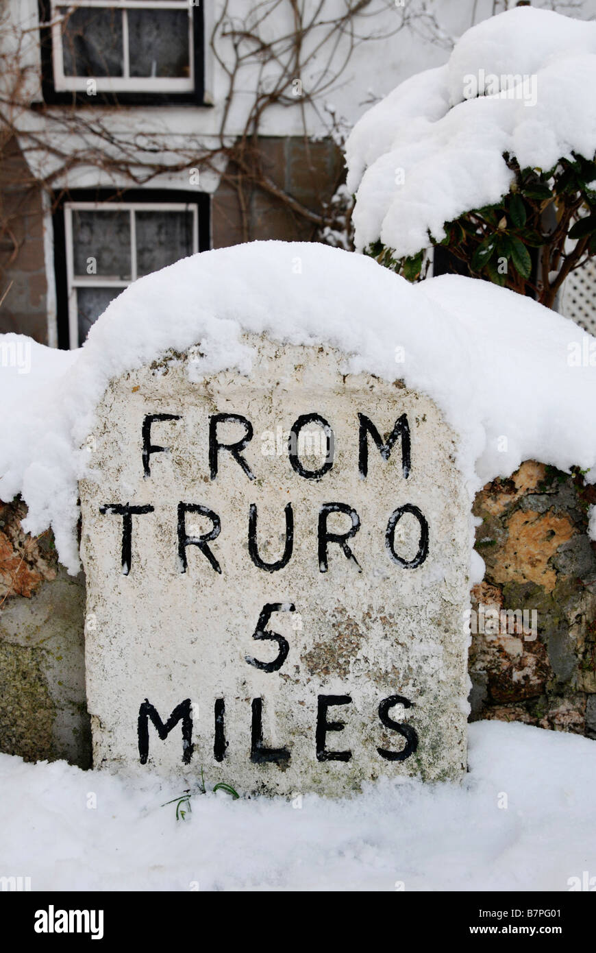 a snow covered milestone,showing 5 miles to truro,cornwall,uk - Stock Image