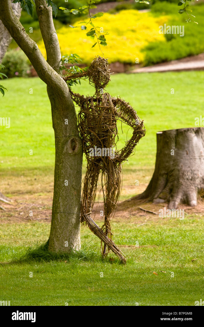 A Wicker statue of a person man leaning against a tree, Ness Gardens, Wirral - Stock Image