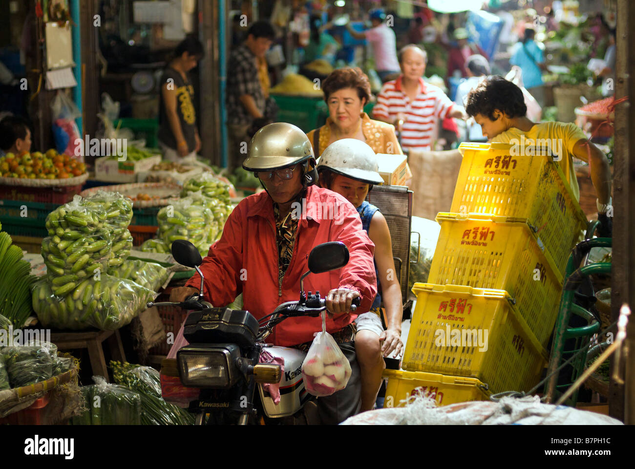 People on motorcycle riding through busy congested alleyway Pak Khlong Talad fresh fruit and vegetable market Bangkok - Stock Image