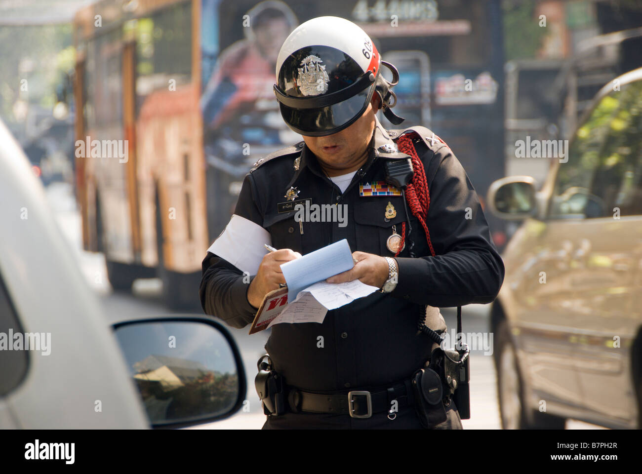 Police traffic control officer writing out a parking ticket Chinatown district in central Bangkok Thailand - Stock Image