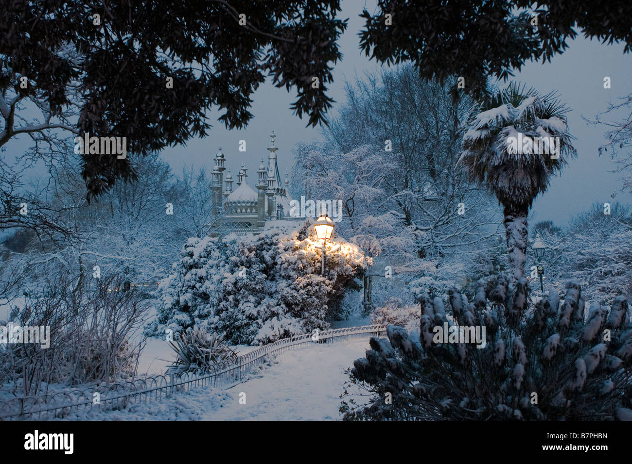 A solitary traditional style period street light illuminates the snow covered gardens of the Royal Pavilion Brighton Stock Photo