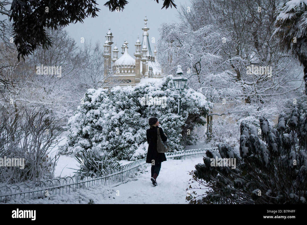 A young woman walks through the snow covered gardens of the Royal Pavilion Brighton in the early morning. Stock Photo