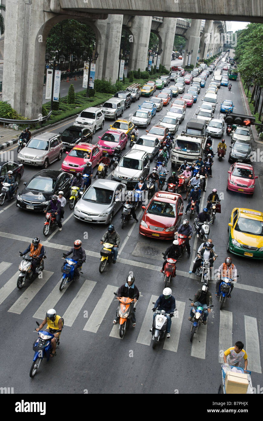 Scooters getting a head start at traffic lights in heavy congestiion Pathumwan district in central Bangkok Thailand - Stock Image