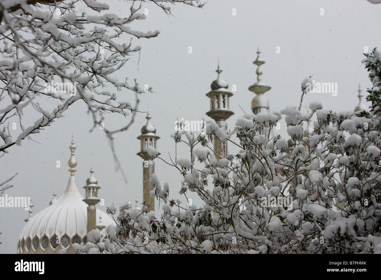 Ornate turrets and dome of the Royal Pavilion Brighton at dawn behind snow covered bushes and tree. Stock Photo