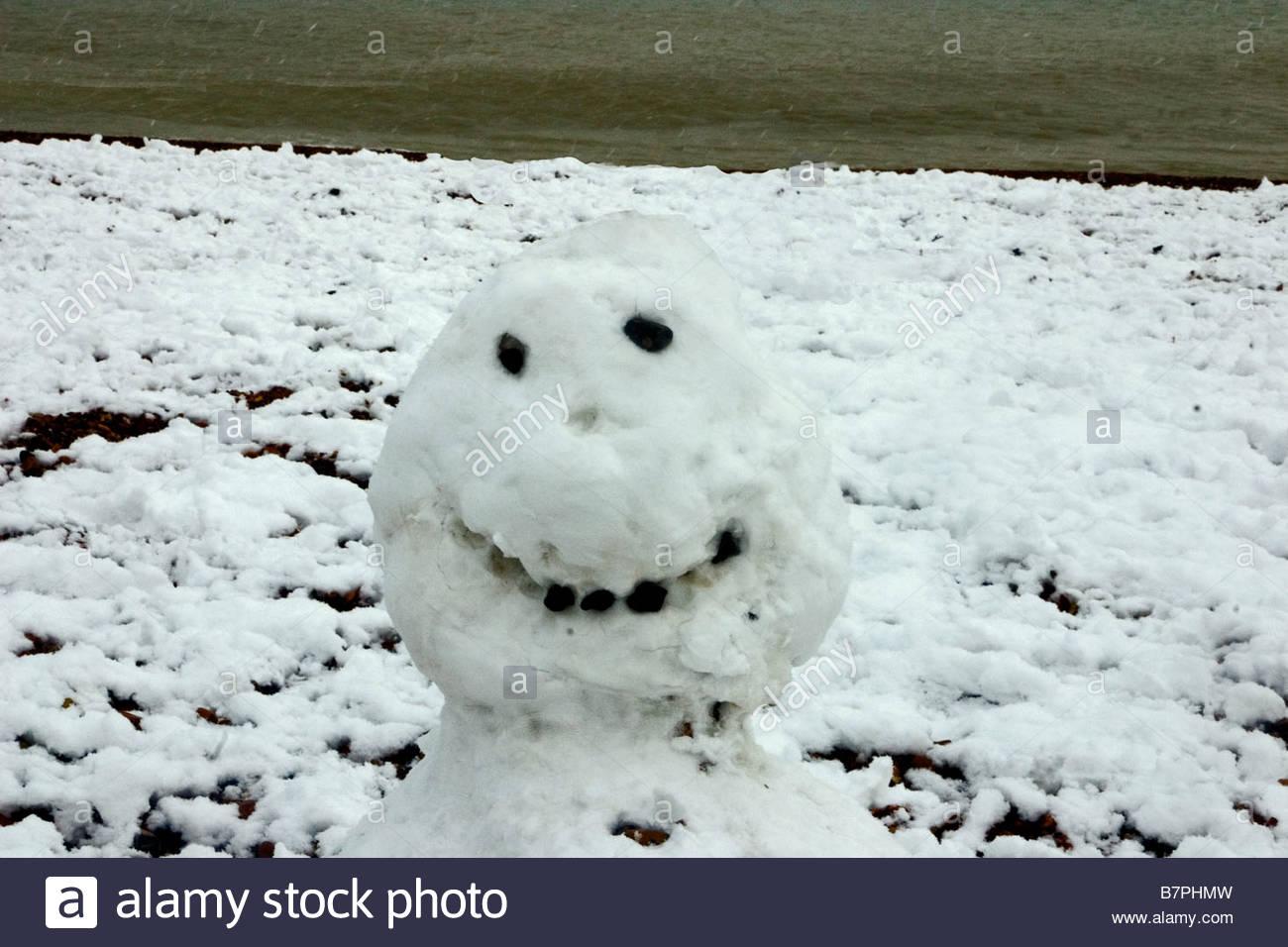 Snowman face on Brighton beach - Stock Image