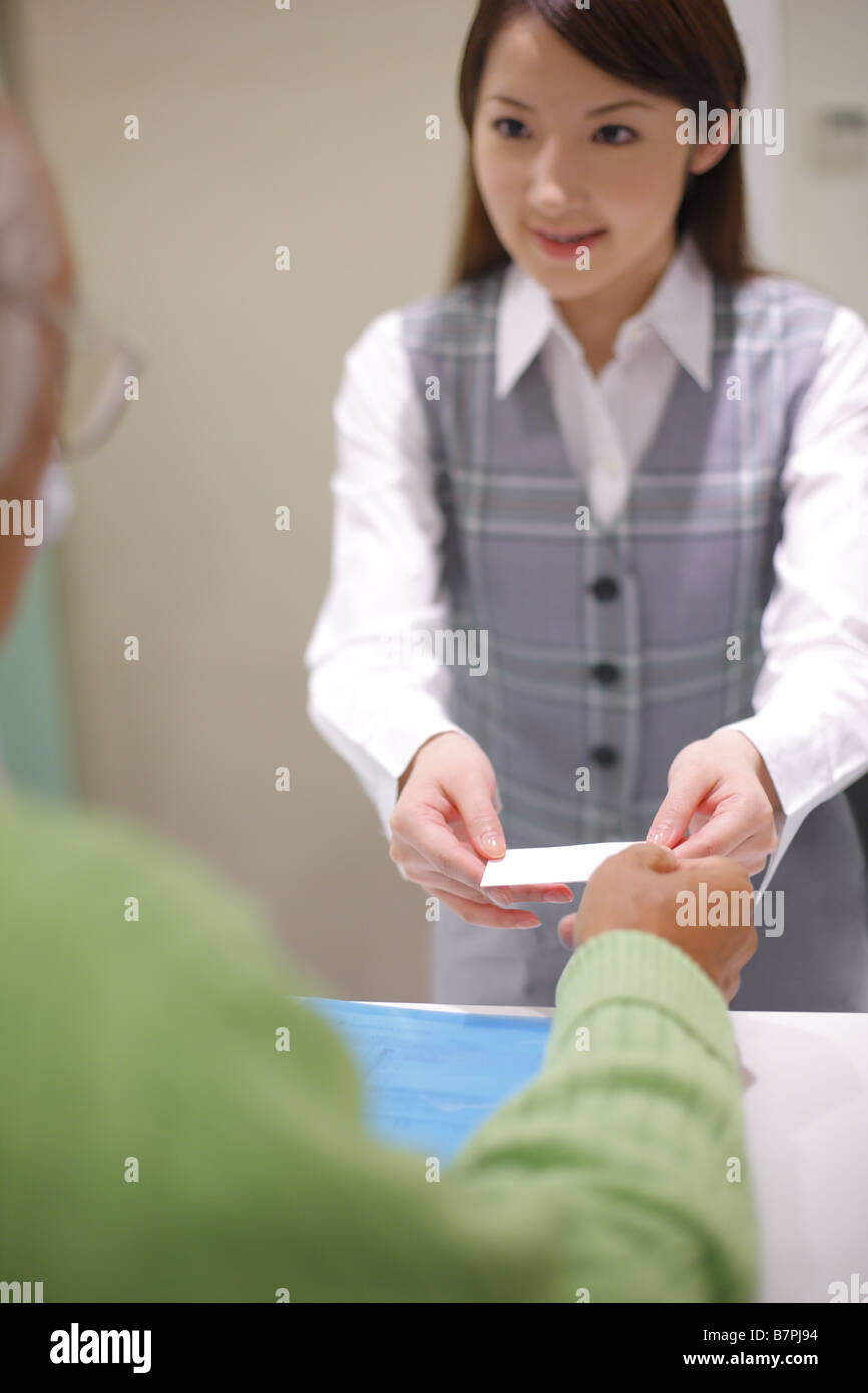 Woman giving patient's registration ticket - Stock Image