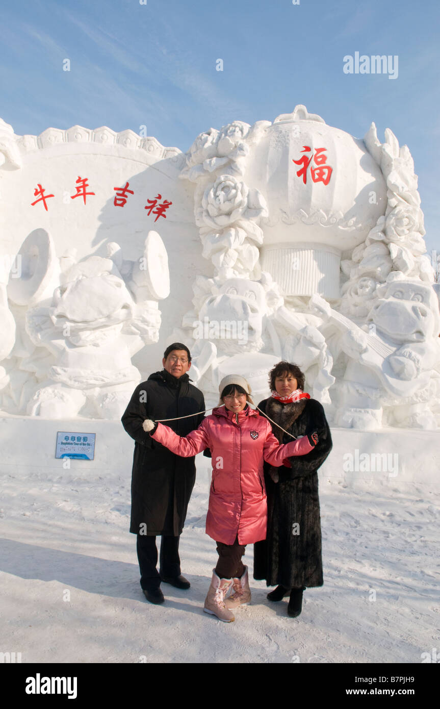 A family poses in front of a sculpture at the Snow and Ice Sculpture Festival at Sun Island Park Harbin Heilongjiang - Stock Image