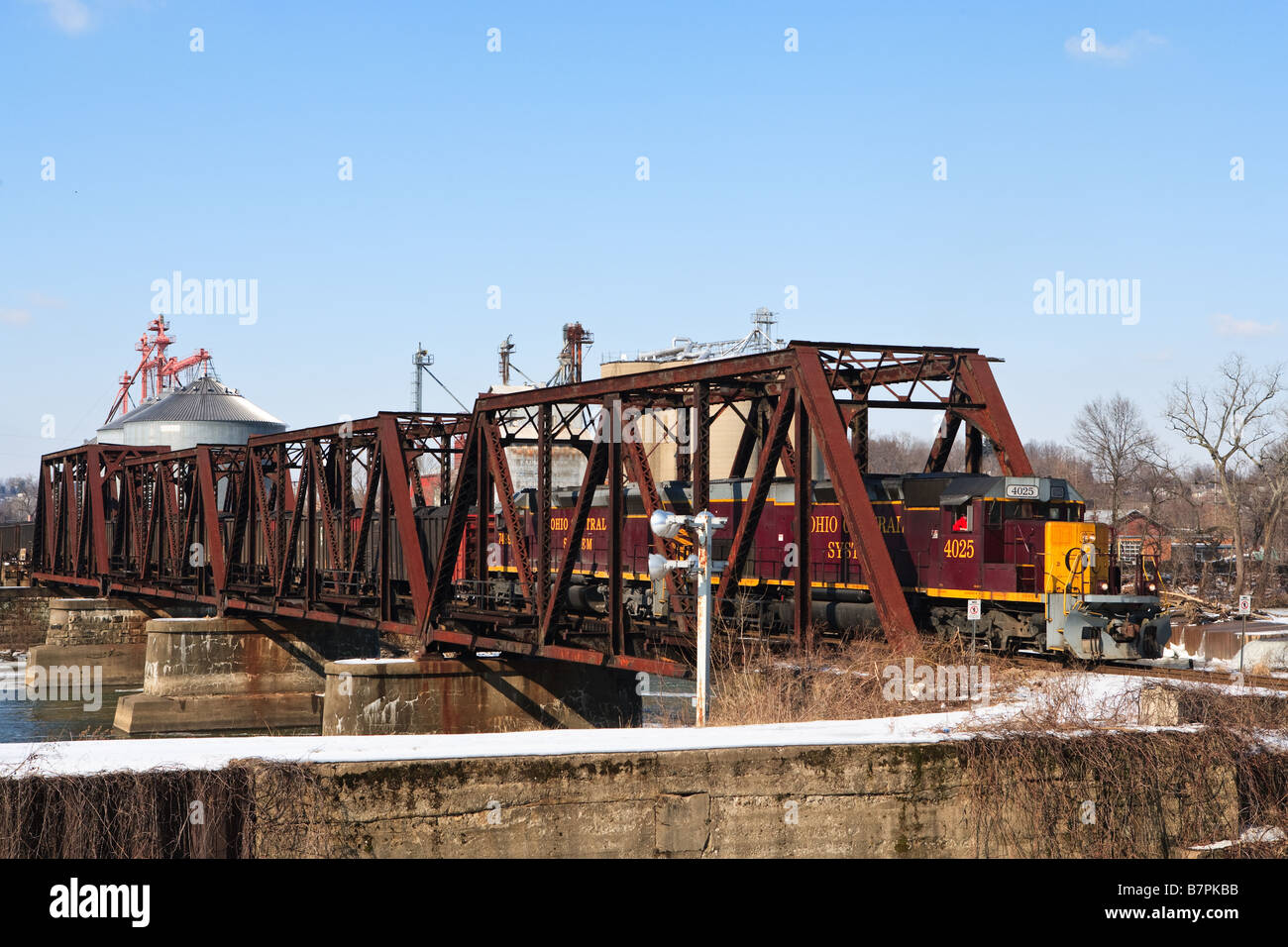 A freight train carrying coal is coming accross a railroad bridge - Stock Image