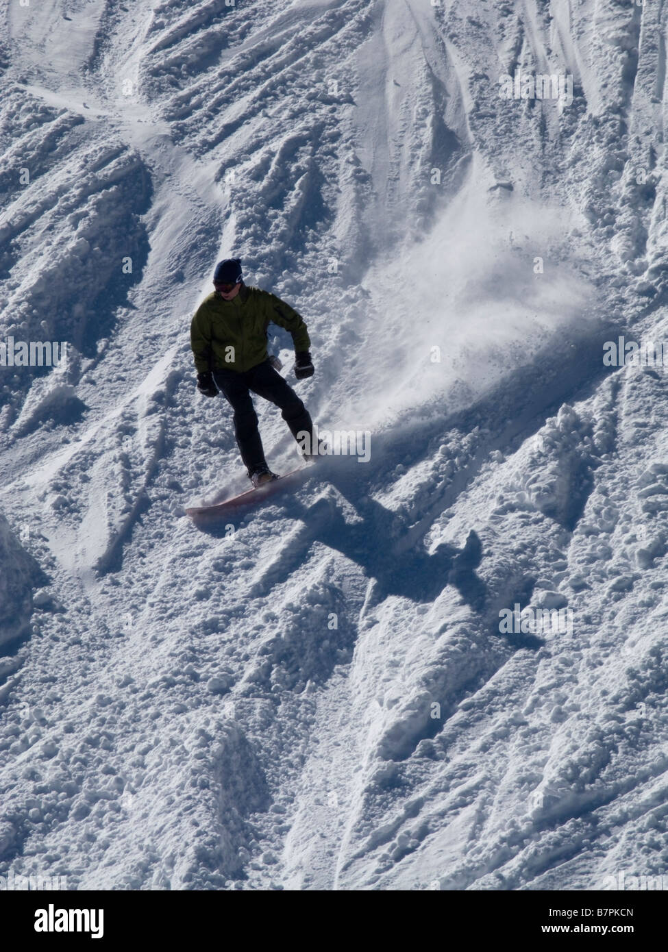 """Snowboarder in the morning sun on the """"Face"""" run at Alpine Meadows Ski Area above North Lake Tahoe, CA. Stock Photo"""