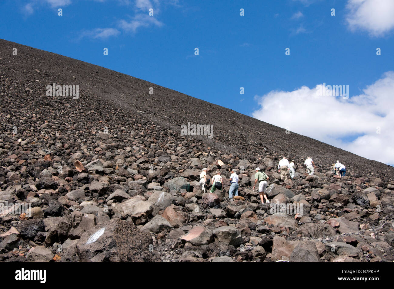 Cerro Negro Volcano with tourists climbing to crater at top of mountain - Stock Image