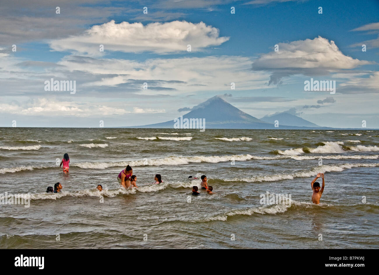 Lake Nicaragua beach north of Rivas with children playing with their teacher, Concepcion and Maderas volcanoes in Stock Photo