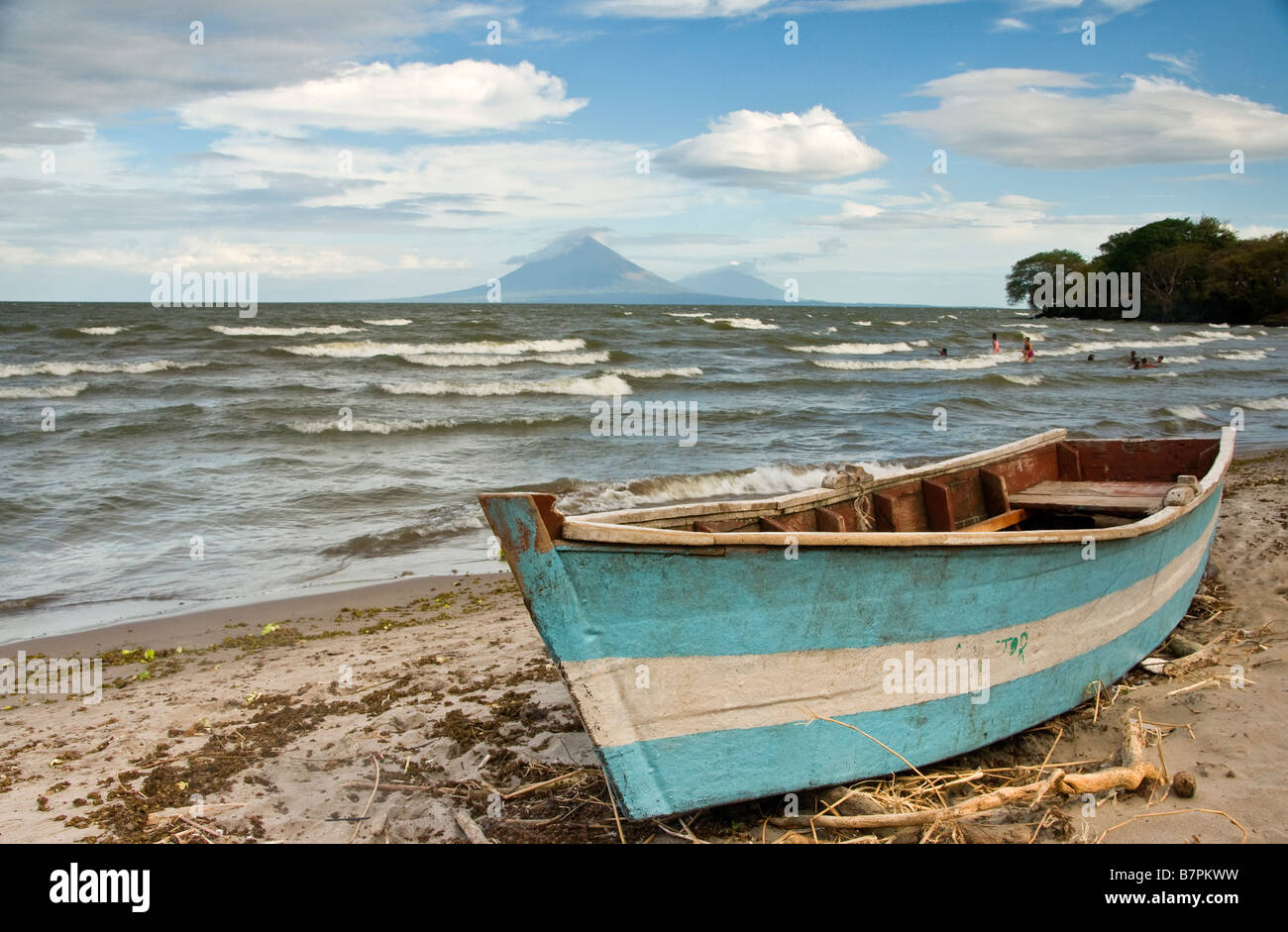 Lake Nicaragua shore north of Rivas with fishing boat, Concepcion and Maderas volcanoes on Ometepe Island in background - Stock Image