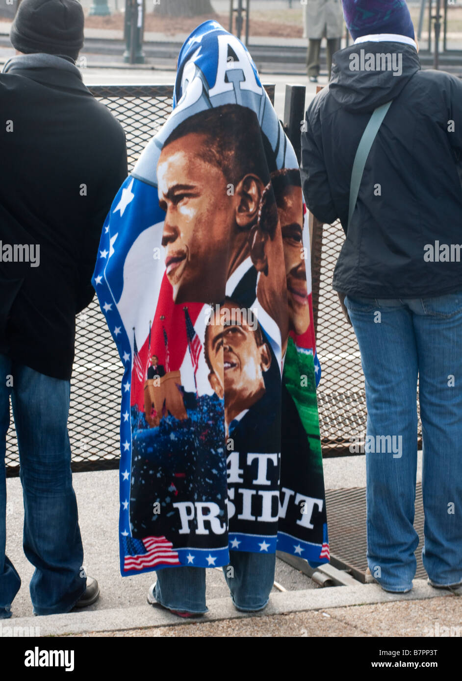A supporter attending the inauguration of Barack Obama keeps warm in a souvenir blanket bearing his image. - Stock Image