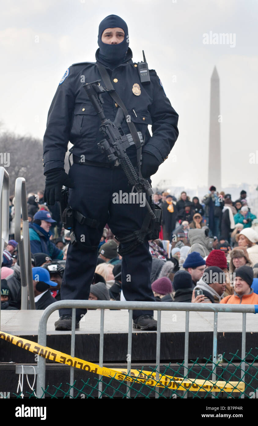 A police officer stands guard with an M4 rifle over a inauguration crowd of 1.8 million people on the National Mall. - Stock Image