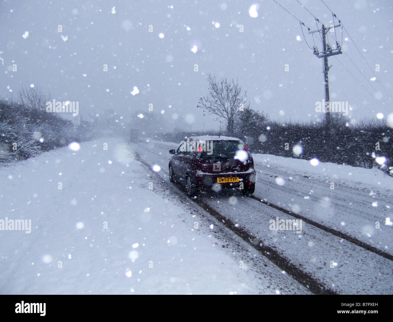 Learner driver in a vauxhall corsa car driving along a snow covered road in rural england - Stock Image