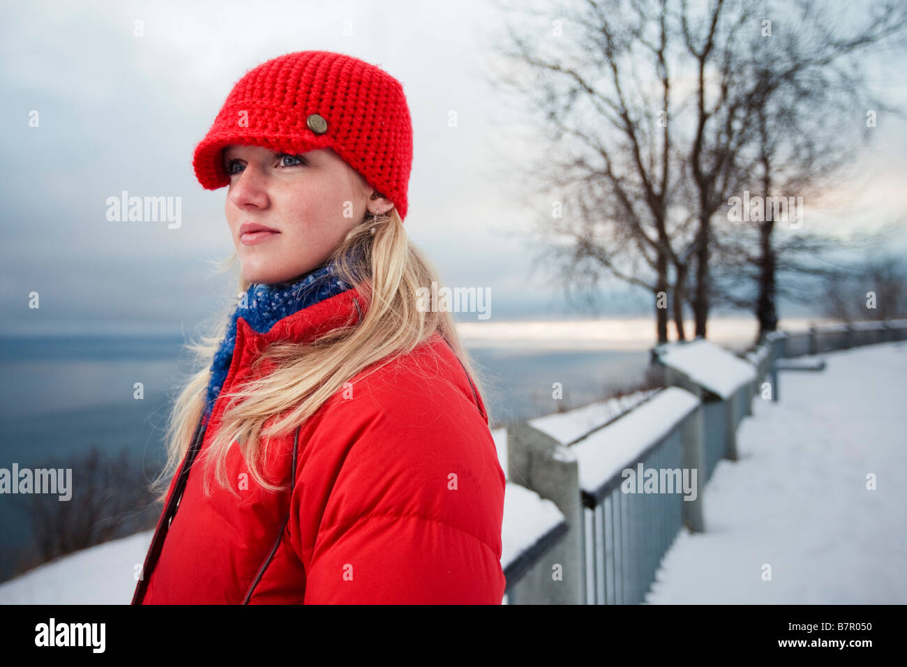 Young woman talks on cell phone at the Baycrest pullout on the sterling highway near Homer, Alaska during Winter - Stock Image