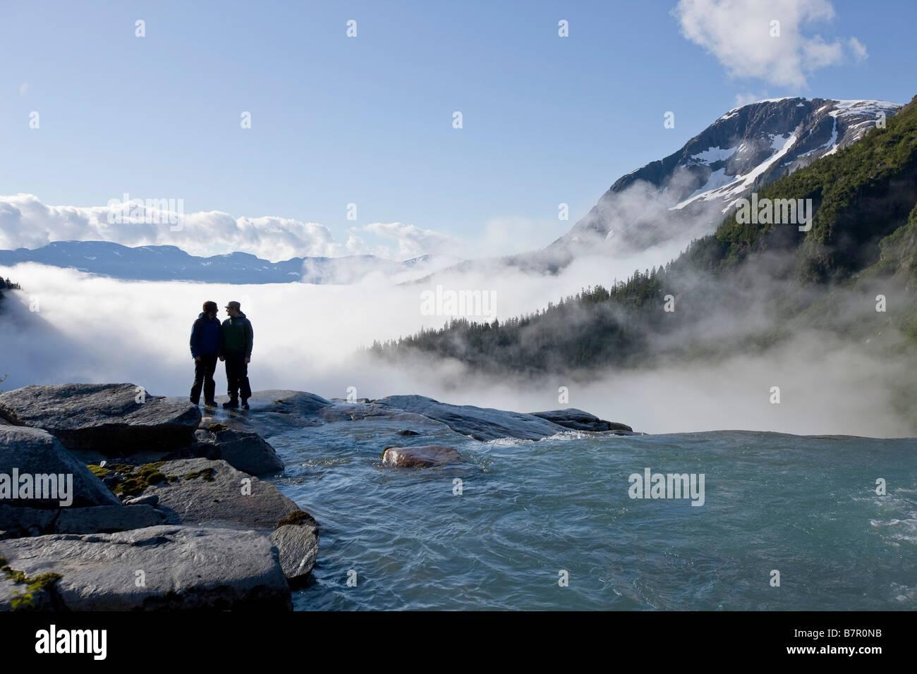Two people overlook the brink of Sockeye Falls originating in the Juneau Icefield, Taku River Valley below in Southeast - Stock Image